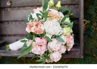 Close up of beautiful lush bridal bouquet of pink and white roses, eustoma and ruscus with satin ribbon in wood box, copy space. Wedding, birthday, holiday concept