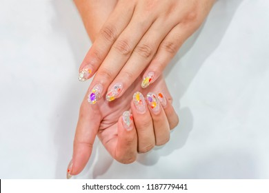 Close up Beautiful Luxury boogie nights nails design with shell,Clear Crystal Sparkle glitter Acrylic extension almond shape fingernails top coat with shiny gel shellac,beautician professional