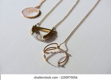 close up of beautiful luxury necklaces and round locket with marble on striped white surface with sunlight