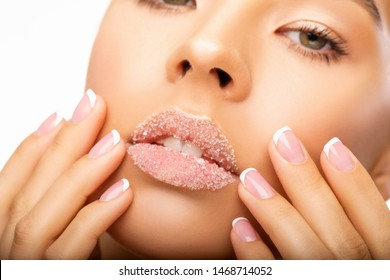 Close up  Beautiful  photo Lip Scrub. Beauty. Lips of Beautiful young Woman covered with Sugar, hands with French manicure touching face Closeup - Image