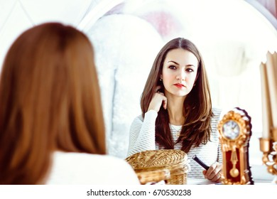 Close up of beautiful pleasant delighted girl sitting in front of the mirror and looking straight while feeling content