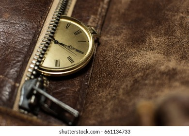 Close up of a beautiful pocket watch. Luxury men's watch placed on a leather background. Fashionable brown leather bag with a watch on top of it.