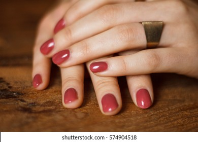 Close up of beautiful polished dark pink nails captured on the wooden table. Fingers are decorated with ring.