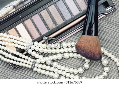Close up of beautiful set of women's fashion accessories and cosmetics, Professional make-up, luxury earings, Makeup brush and cosmetics. (Vintage Style Color)