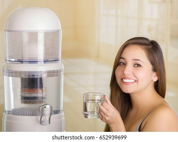 Close up of a beautiful smiling woman holding a glass of water, with a filter system of water purifier on a kitchen background