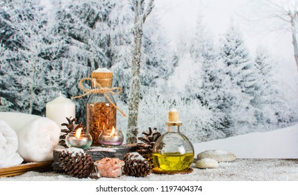 Close up of beautiful spa composition in wellness center, Towels on massage table in spa salon setting. Spa feet & hand massage compress balls, aromatherapy oil in winter with snowflake and Pine cones