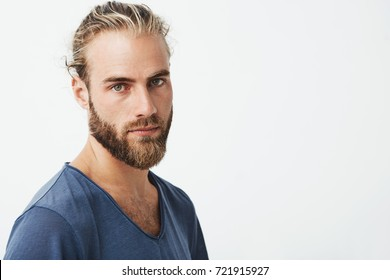 Close up of beautiful swedish man with stylish hairstyle and beard in blue t-shirt looking in camera with serious expression.