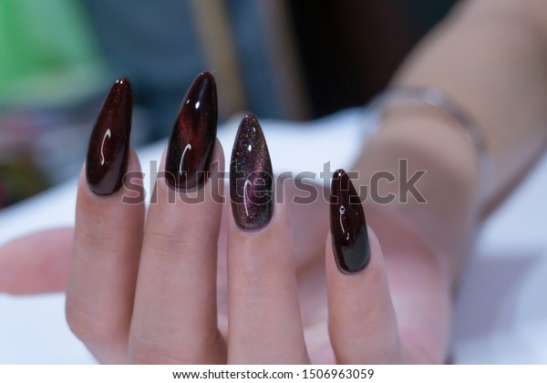 Close up Beautiful Trendy Mysterious Dark Red and Multicolor Cat's eye Gel Nail Design on woman Acrylic Extension Stiletto Style Fingernail,Nail Art idea for Halloween