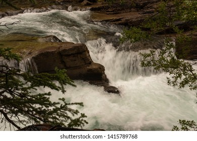 A close up of a beautiful waterfall cuts through the rocks at Maligne Canyon, Jasper National Park, Canada, short exposure to capture the power of the waterfall