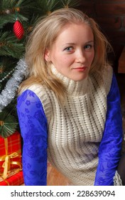 Close up of beautiful woman in  blue lace blouse and white sweater sitting by a Christmas tree