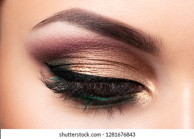 Close up of beautiful woman eye with multicolored smokey eyes makeup. Modern fashion make up. Studio shot