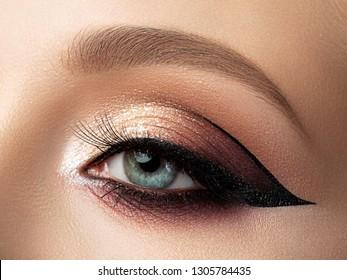 Nahaufnahme eines schönen weiblichen Auges mit mehrfarbigem Modeschminken und modernem Wimpernflügel. Studioaufnahme