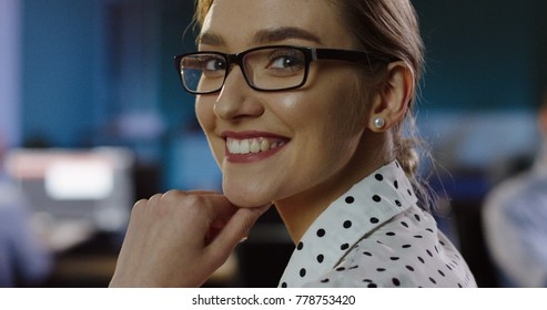 Close up of beautiful woman in glasses looking at office space behind her, than turning the head to the camera and smiling sincerely. Late in the evening. Indoor. Portrait