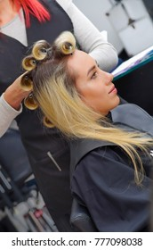 Close up of beautiful woman in a hair salon with a stylist working with curlers in the head, in a hair salon background