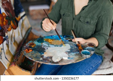 Close up beautiful woman hands holding paint brush drawing amazing picture on canvas in modern cozy art workshop