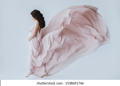 Close of beautiful woman with long curly brunette hair, wearing in long pink pale dress, posing at white isolated studio. Pregnant happy girl, expecting and anticipation to baby. Concept of motherhood