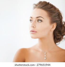 close up of beautiful woman wearing shiny diamond necklace