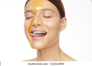 Close up beautiful women portrait, honey flowing down on her face and she is licking it. Clean perfect face. White background and studio light.