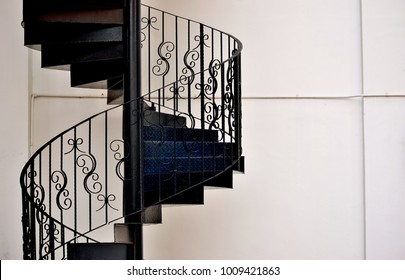 Close up of beautiful wrought iron exterior spiral staircase on the side of a shop house in Singapore with copy space for design