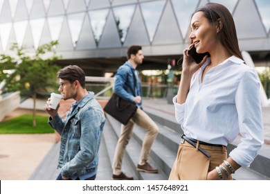 Close up of a beautiful young asian woman talking on mobile phone while walking down the stairs at the city street surrounded by crowd
