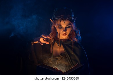 Close up of beautiful young beginner witch doing magic among smoke. Red haired attractive elf in silver tiara learning spells from book. Charming girl casting spell and making fog around herself.