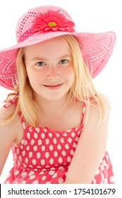 Close up of beautiful young blonde girl with enigmatic smile wearing a big pink floppy hat and looking directly at the camera. Isolated on white studio background