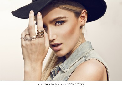 Close up of beautiful young  blonde woman with black hat. Wearing denim vest. Her hair is tied to ponytail. Professional make-up, hair style and styling.