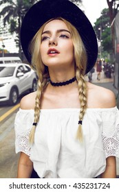 Close up of beautiful young blonde woman with black hat walking on the street. Her hair is tied in two big ponytails. Around neck she has black choker. Professional make-up, hair style and styling.