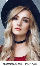Close up of beautiful young blonde woman with black hat, looking at camera. She has long curly golden hair and wearing red t-shirt. Around neck she has black choker.