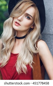 Close up of beautiful young blonde woman with black hat, looking at camera and touching her long curly golden hair. She is wearing red t-shirt, around neck she has black choker
