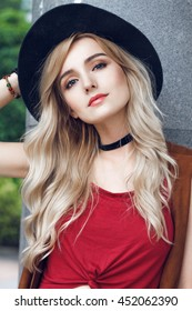 Close up of beautiful young blonde woman with black hat, looking at camera. She has long curly golden hair and wearing red t-shirt. Around neck she has black choker
