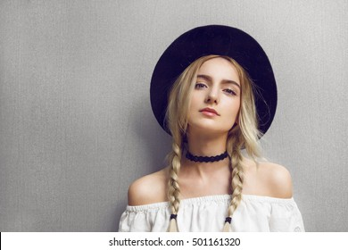 Close up of beautiful young blonde woman with black hat. Her hair is tied in two big ponytails. Around neck she has black choker. Professional make-up, hair style and styling.