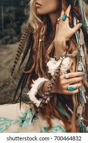 close up of beautiful young boho hands with feathers