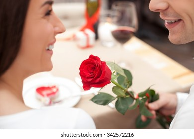 Close up of beautiful young loving couple celebrating Valentine day in cafe. The man is giving to a woman a rose. They are sitting at the table and smiling