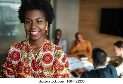 close up of beautiful young smiling professional black african business woman, coworkers hold a meeting in background - Shutterstock ID 1684422238