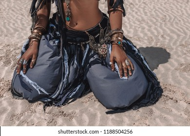 close up of beautiful young stylish tribal dancer in oriental costume sitting on sand outdoors