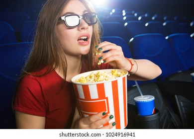 Close up of a beautiful young woman in 3D glasses enjoying watching action movie at the cinema grabbing popcorn from the bucket copyspace expressive fascinated entertaining showtime spectator.