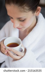 Close up of a beautiful young woman in bathrobe having tea