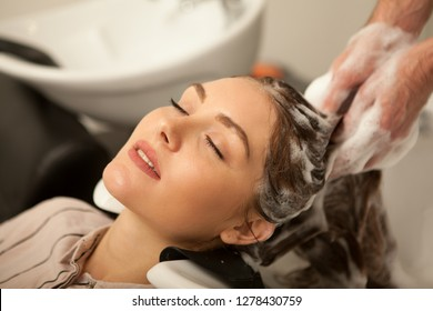 Close up of a beautiful young woman enjoying head massage with her eyes closed, while professional hairdresser washing her hair with shampoo. Hairstylist working with his female client