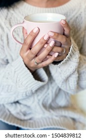 Close up of a beautiful young woman hands holding a cup of hot coffee in winter outfit at home