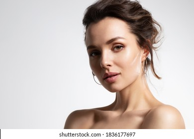 Close up of beautiful young woman with healthy soft glowing skin and bare shoulders in studio isolated on white background. Advertising poster for skincare cosmetics and rejuvenation procedure