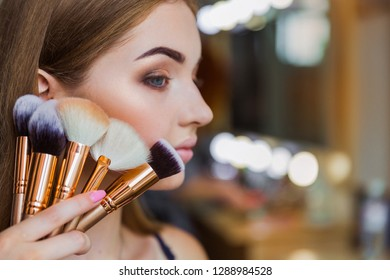 Close up the beautiful young woman holding the make-up brushes in hand near her cheek indoors