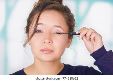 Close up of beautiful young woman holding a eyeliner and doing crazy make-up in her face, in a blurred background