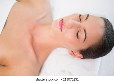 Close up of a beautiful young woman lying on massage table at spa center