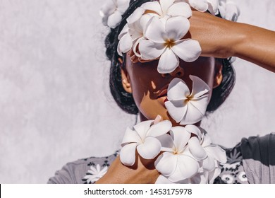 close up of beautiful young woman wearing wreath and holding frangipani flowers near face at white background