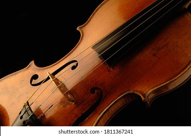 Close up beautifully aged 200 year old antique french violin isolated on black background