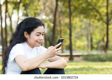 close up beauty asian woman in white shirt and use smartphone on blur background