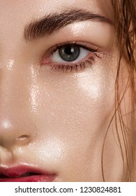Close up beauty of a half face of a woman with wet radiant skin and big gray eyes. Fashionable natural makeup and wet facial hair. Pink lipstick with kissed lips