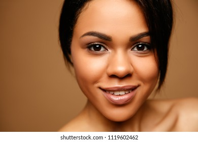Close up Beauty Portrait of attractive African American young spa woman with perfect skin and natural make up. Beautiful brunette model. Skin  Care Concept. Looking on camera against brown background
