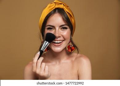 Portrait de beauté en gros plan d'une jeune femme séduisante topless portant le bandeau sur fond marron, tenant une brosse à maquillage